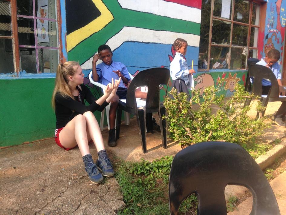 Norsk elev hjelper en av barna med leksene